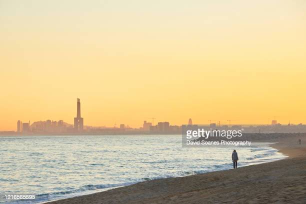 a beach at sunset in barcelona, spain - la barceloneta stock-fotos und bilder