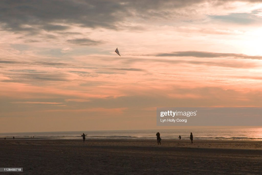 Beach at sunset with figures silhouetted flying a kite : Stock Photo