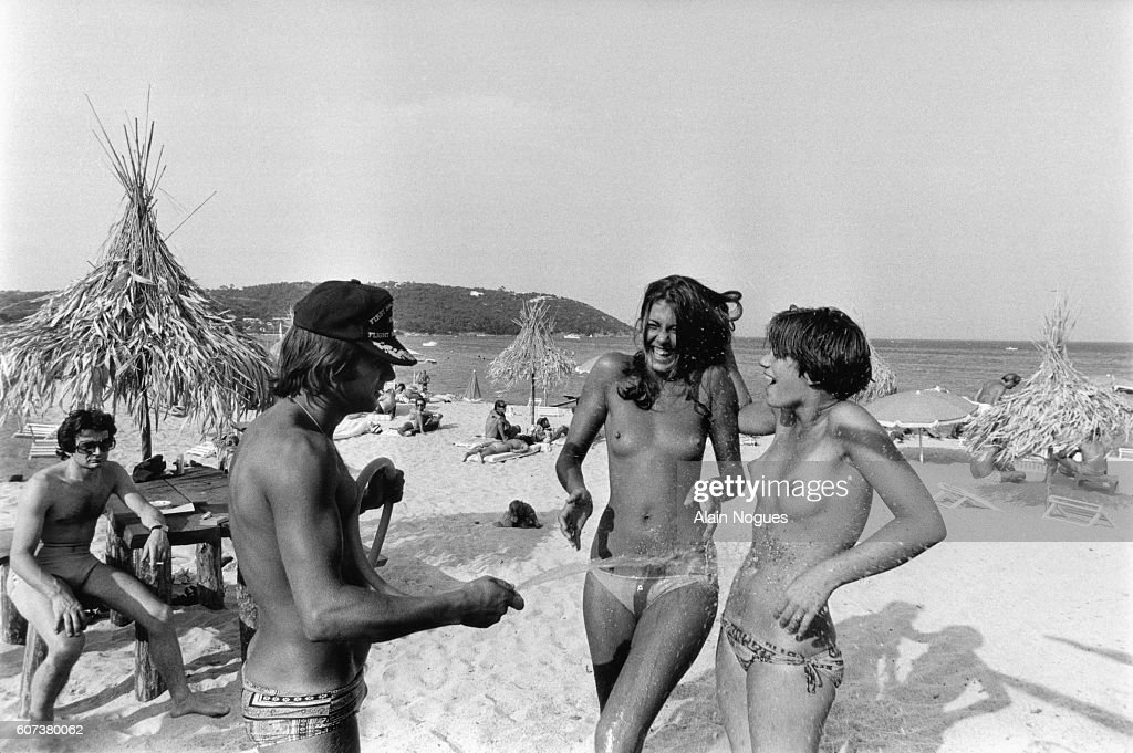 A beach attendant at La Voile Rouge beach bar waters two topless girls with a hose on a St.-Tropez beach.