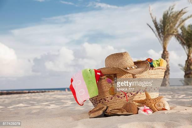 Beach bag and hat, sunglasses, flip flops, towels
