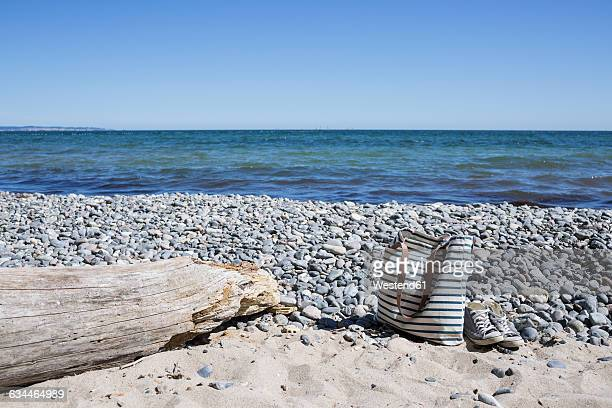 Beach bag and sneakers standing on a beach pebble beach