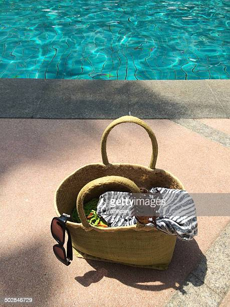 Beach bag with sunglasses by swimming pool