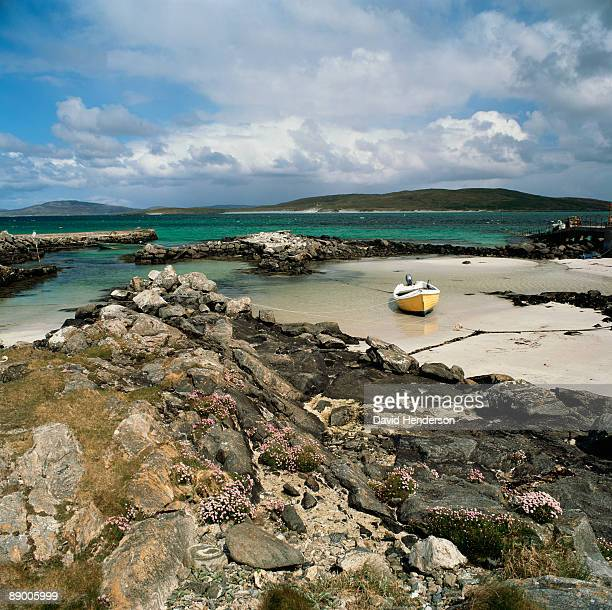 beach boat on rocky seashore, barra, outer hebrides, scotland - barra scotland stock pictures, royalty-free photos & images