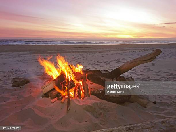 beach bonfire at dusk with the pacific ocean in the background. - manzanita stock pictures, royalty-free photos & images
