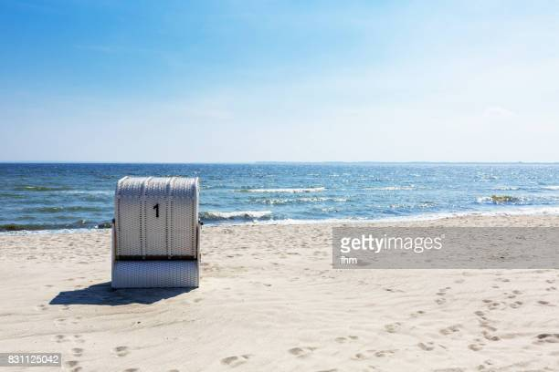beach chair nr. 1- one beach chair on the empty beach - schleswig holstein stock photos and pictures