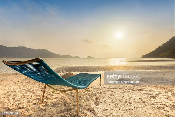 Beach chair on a tropical beach during sunset. - Shallow of focus