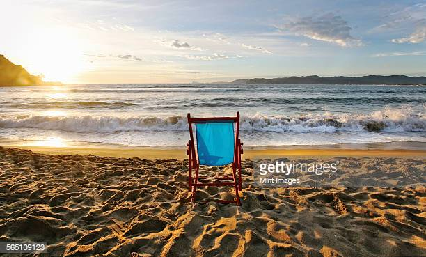 A beach chair on the sand and a sunset on the horizon.