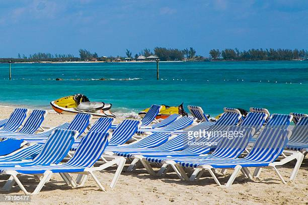 beach chairs and jet boats on the beach, cable beach, nassau, bahamas - cable beach bahamas stock photos and pictures