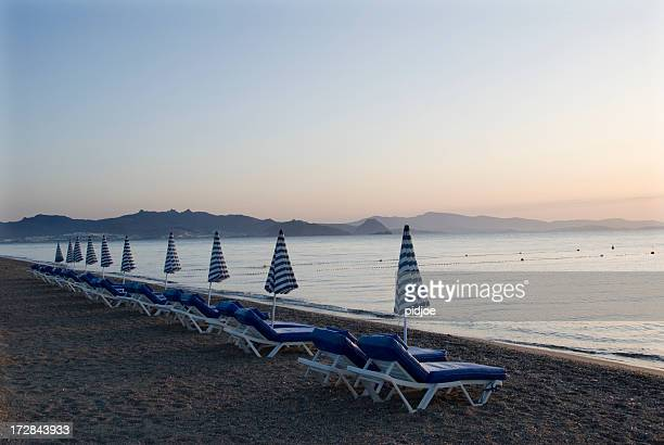 beach chairs and parasols at dawn