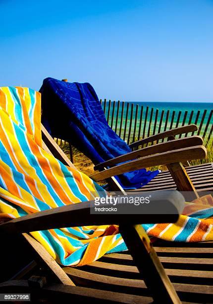 Liegestühle am Strand mit dem Meer im Hintergrund