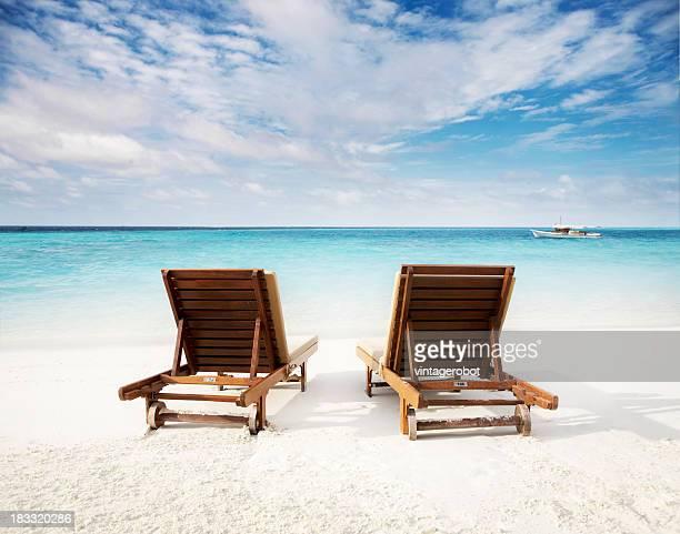 Beach chairs on waters edge