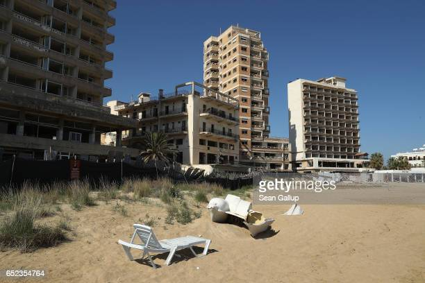 Beach chairs stand on a public beach in the Turkish Republic of North Cyprus next to former, decaying hotel buildings that stand inside the...
