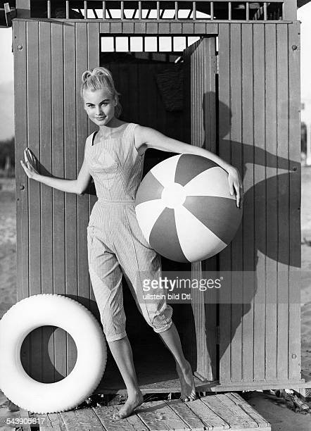 Beach fashion Model dressed in a trousers costume with a ball and bathing ring on the beach ca 1957 Photographer Regine Relang Published by...