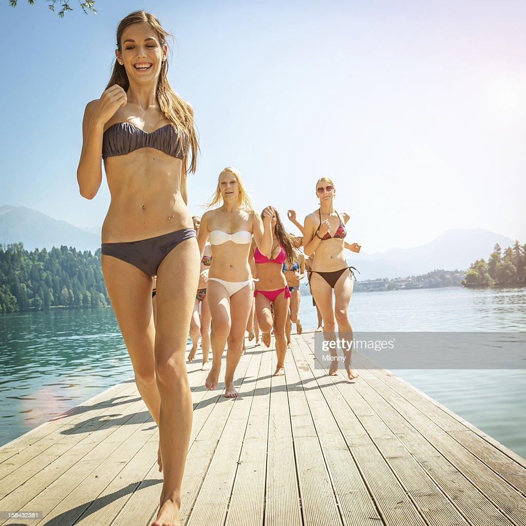 Beach Girls Running over Jetty : Stock Photo