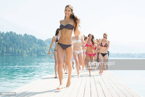 beach girls walking along on jetty at the lake - lake bottom stock photos and pictures