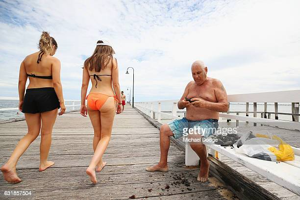 A beach goer shells his mussels taken from the piers pylons at South Melbourne Beach on January 17 2017 in Melbourne Australia Temperatures reached...