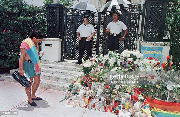 A beach goer stops to read and look at notes and flower arrangements left by wellwishers on the steps of the house of slain Italian designer Gianni...