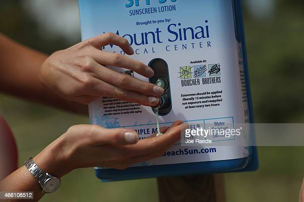 A beach goer tries a squirt of sunscreen from one of 50 sunscreen dispensers that are being setup along the beach on March 13 2015 in Miami Beach...