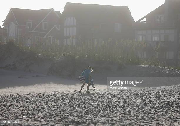 A beach goer walks away as winds pick up from approaching Tropical Storm Arthur July 2 2014 in Cape Hatteras North Carolina A hurricane warning has...
