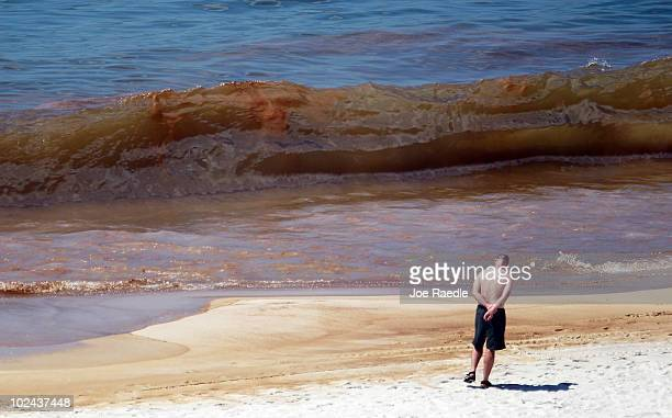 A beach goer walks on the beach where oil is seen in the water as it washes ashore from the Deepwater Horizon oil spill in the Gulf of Mexico on June...