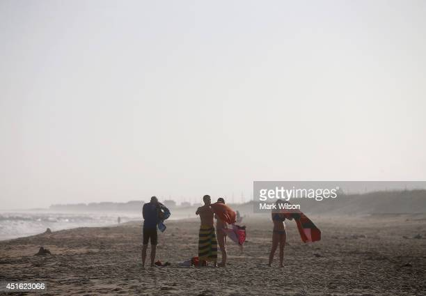 Beach goers dry off as winds pick up from approaching Tropical Storm Arthur July 2 2014 in Cape Hatteras North Carolina A hurricane warning has been...