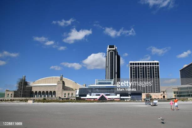 Beach goers in front of Trump Plaza Hotel and Casino, once one of the city's premier destinations, now under demolition on September 30, 2020 in...