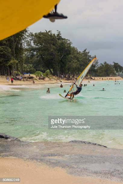 Beach Goers in Swimsuits Enjoy Watching Recreation Kiteboarding Windsurfers and Kayakers in the Teal Colored Pacific Ocean at the Vacation Travel...