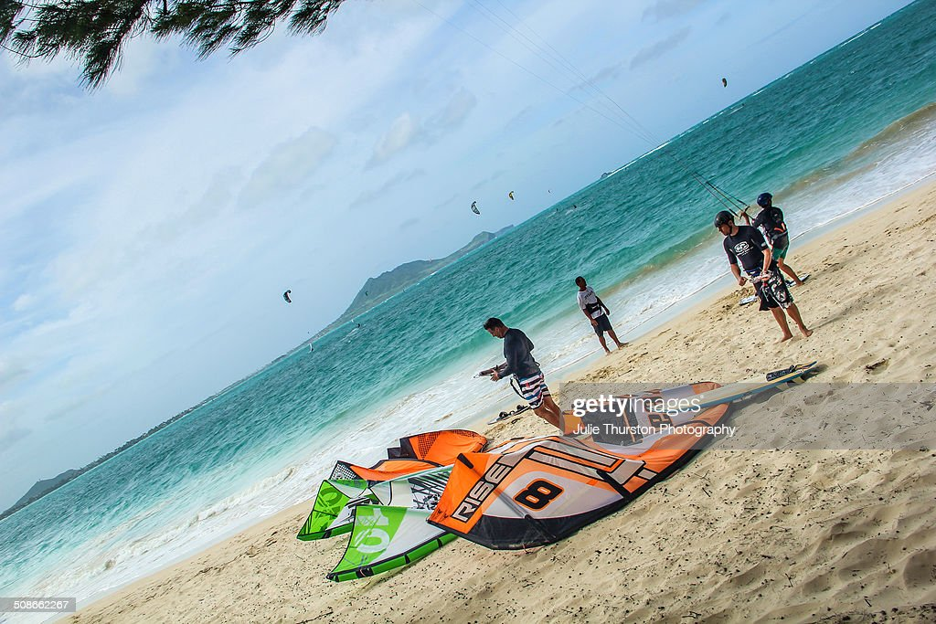 Beach Goers in Swimsuits Enjoy Watching Recreation Kiteboarding and Kayakers in the Pacific Ocean With The Mokapu Penninsula in the Distance at the Vacation Travel Destination of Kailua Beach on the Island of Oahu