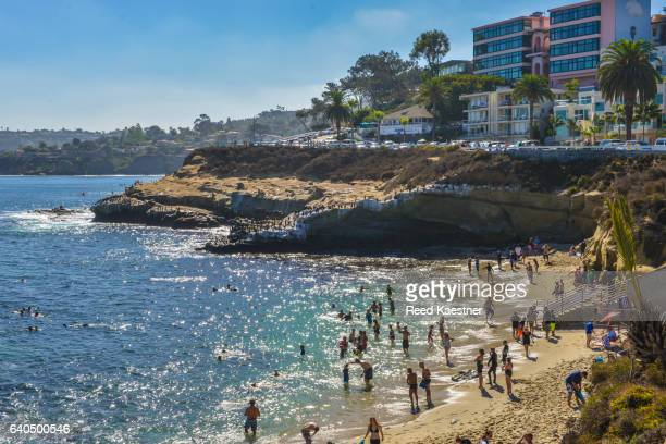 beach goers line the shore at the famous cove at la jolla, california, a poular swimming location. - la jolla stock pictures, royalty-free photos & images