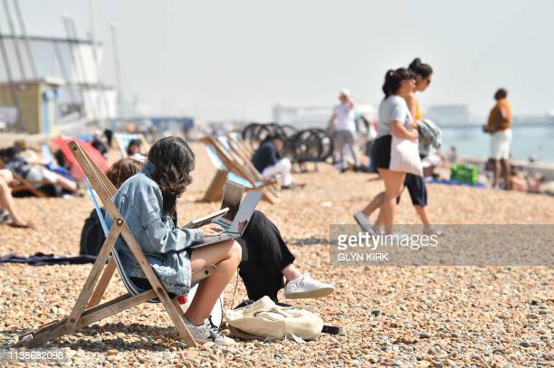 Beach goers relax by the sea in Brighton southern England on April 22 2019 as Britain enjoys an unseasonably warm Easter Bank Holiday weekend