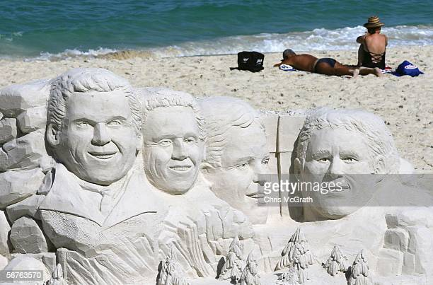 Beach goers sunbathe behind a two metre high sand sculpture showing the faces of golfers Colin Montgomerie Retief Goosen Adam Scott and Michael...