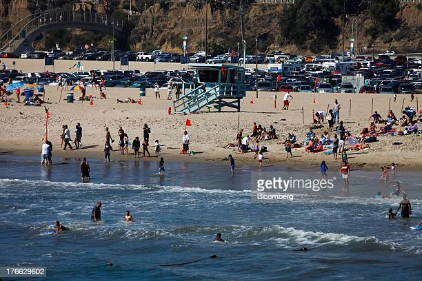 Beach goers swim in the Pacific Ocean near a lifeguard tower north of the Santa Monica Pier in Santa Monica California US on Monday Aug 5 2013...