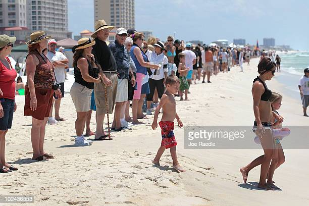 Beach goers walk past others standing together during a Hands Across The Sand event at the beach on June 26 2010 in Pensacola Florida The event was...