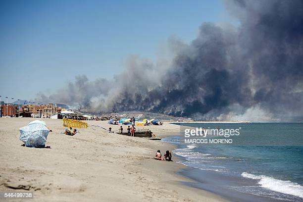 TOPSHOT Beach goes sunbath as smoke from forest fire rises above Levante de La Linea beach in the southern Spanish region of Cadiz Andalusia on July...
