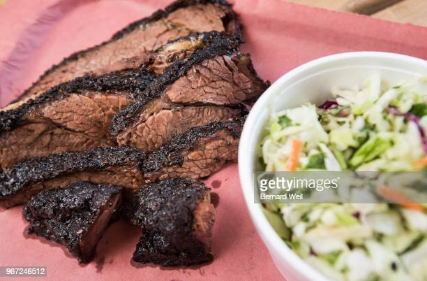 Beach Hill Smokehouse owner Darien List and pitmaster Terrence Hill show off their succulent sliced brisket and coleslaw on paperlined tray