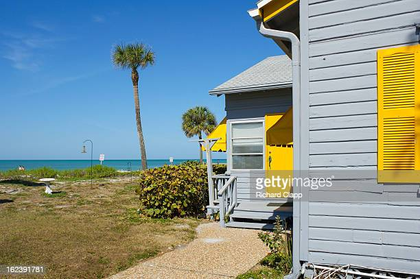 CONTENT] Beach home on the Gulf of Mexico at Siesta Key FL View shows bright yellow shutters on a grey home