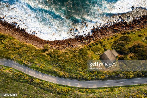 beach house close to a rocky coastline with crashing waves - rocky coastline stock pictures, royalty-free photos & images