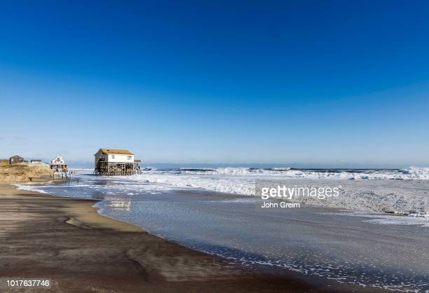 Beach house on stilts surrounded by high tide storm surf