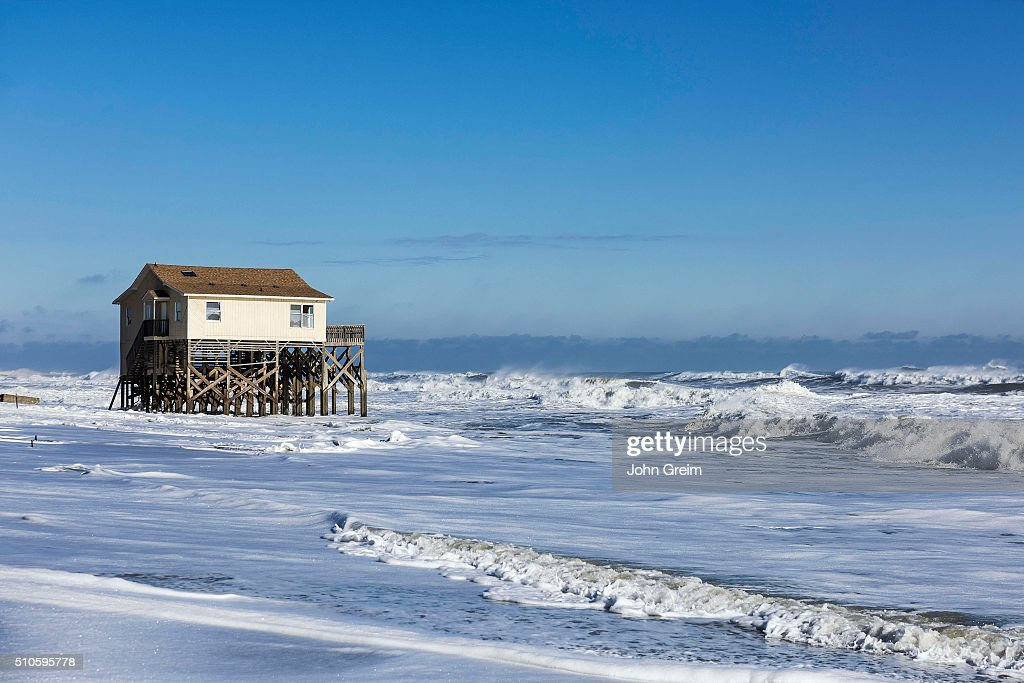 Beach house on stilts surrounded by high tide surf Pictures