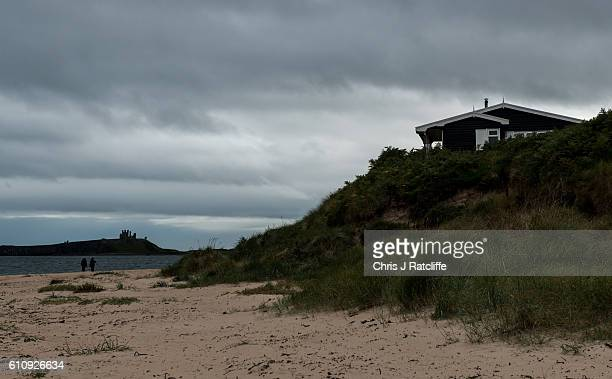A beach house sits on top of sand dunes in Embleton Bay as dark storm clouds form over Dunstanburgh Castle on the coast of Northumberland on...