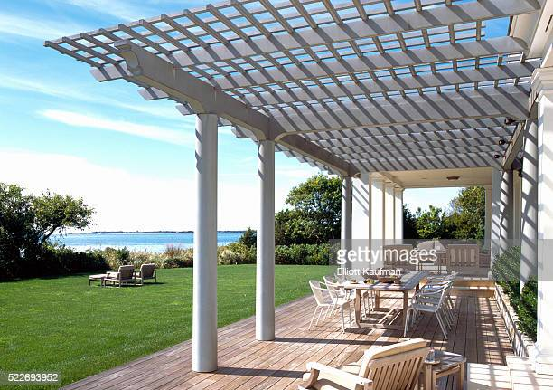 A beach house with pergola and lounge chairs