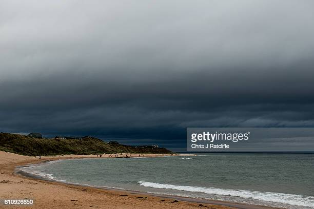 Beach houses sit on top of sand dunes in Embleton Bay as dark storm clouds form on the coast of Northumberland on September 28 2016 in Craster...