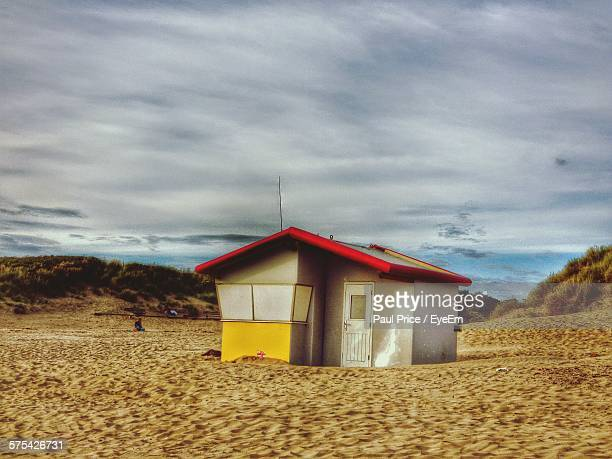 beach hut against cloudy sky - llanelli stock pictures, royalty-free photos & images