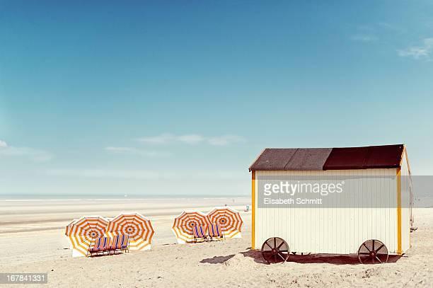 Beach hut and several sun shades along beach