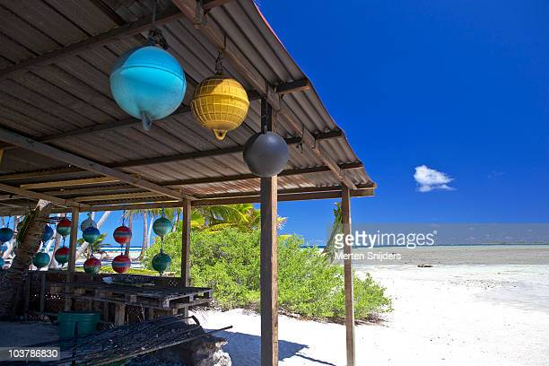 beach hut decorated with hanging buoys at motu around blue lagoon. - merten snijders stockfoto's en -beelden