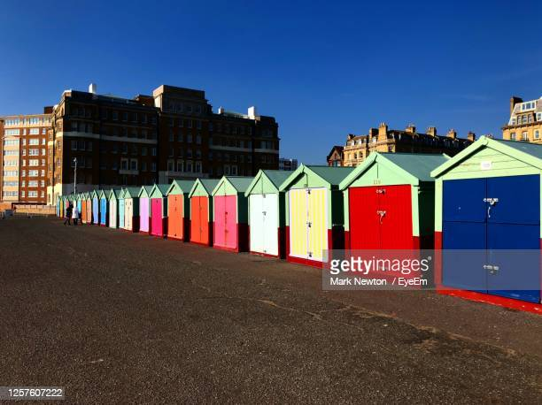 beach huts against buildings in city - hove stock pictures, royalty-free photos & images