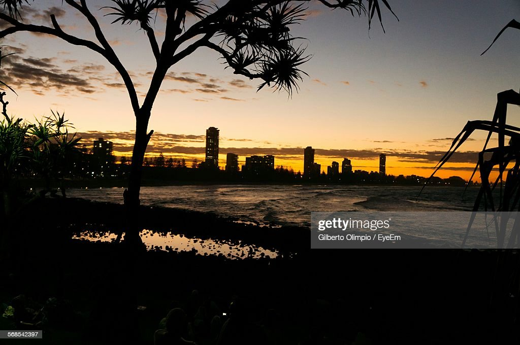 Beach In Front Of Cityscape Against Sky During Sunset : Stock Photo