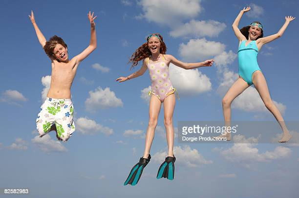 Beach kids jumping for joy