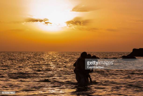 Beach marriage with traditional bathing of bride and groom in the sunset at Rena Majore beach on September 9 2014 in Cagliari Sardinia Italy