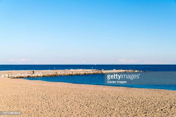 beach of barcelona with blue sky and sand beach - la barceloneta stock-fotos und bilder